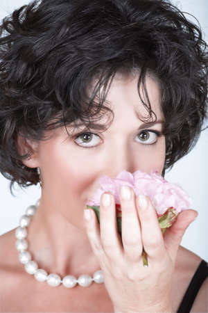 early 40s: Woman with black curly hair smelling a pink peony flower, in her mid 30s early 40s  Stock Photo