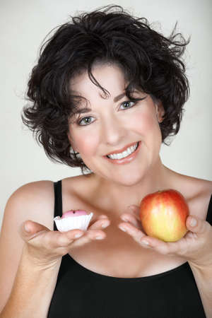 Beautiful mature woman in her late 30s early 40s choosing between an apple and a cake  photo