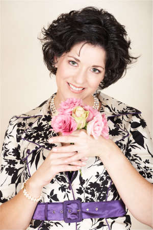 early 40s: Happy woman with black curly in black and white fashion jacket, holding spring flowers in pink and green, mid 30s, early 40s