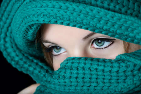 eye liner: Young woman with black kohl make-up on eyes in traditional Middle East fashion covering her face with green scarf