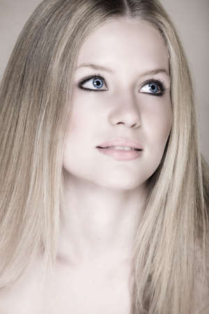 Young beautiful teenage girl with long blond hair, blue eyes and natural make-up. Low-key effect. Visible clear skin texture with pores