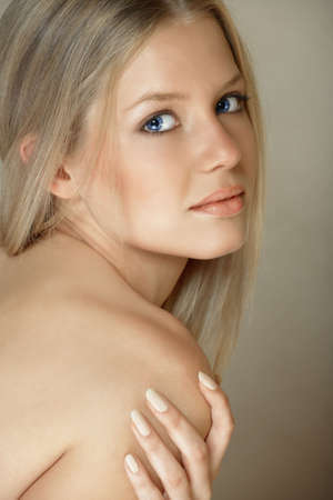 young woman with long blond hair and bare shoulder looking into the camera