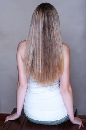 back straight: Young woman with long straight blond hair sitting in studio with her back - low key lit background  Stock Photo