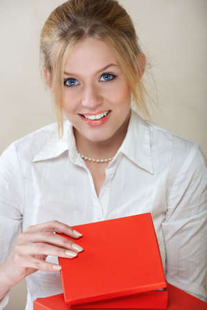 Young beautiful businesswoman with blond hair and blue eyes in white shirt opening a red box  photo