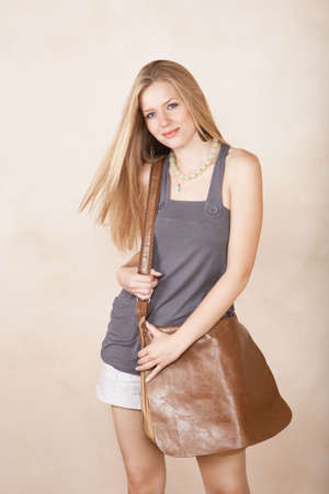 Blond girl with long hair in summer top and shorts smiling on studio background  photo