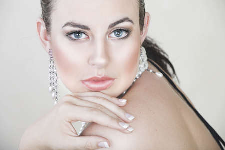Glamour portrait of beautiful young brunette woman with pearl and silver jewelry