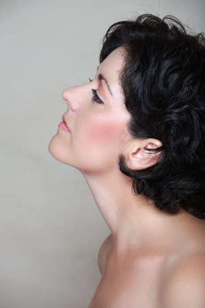 Beautiful woman in her early 40s late 30s with short curly black hair, in profile. Visible clear skin texture with pores and fine lines appropriate to her age, natural make-up