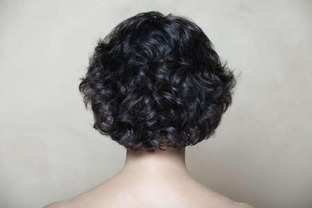 a bob: Mujer con el pelo rizado negro en fondo amarillento de la textura