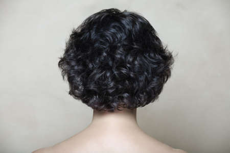 'head and shoulders': Woman with black curly hair on beige texture backgroundr
