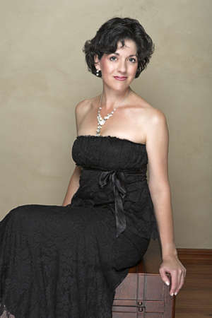 30s thirties: Beautiful happy adult woman with black curly hair and soft natural make-up, wearing black evening or cocktail dress and fashion pearl accessories