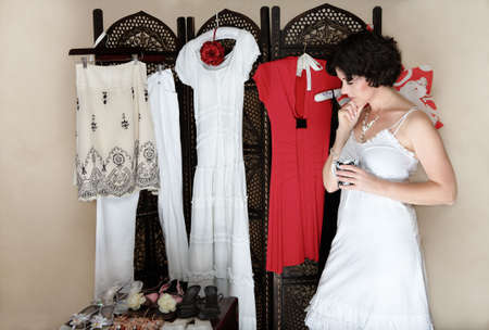 Woman in her 30s-40s standing next to a collection of shoes and other hanging clothes � thinking