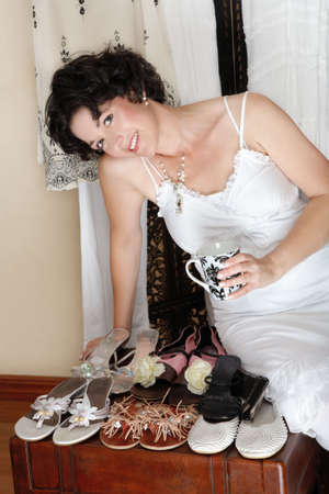 Woman with short brown hair sitting next to her shoe collection with cup a coffee and smiling, in her mid 30s, early 40s Stock Photo - 2955792