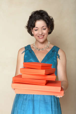 Beautiful woman in blue fashion dress holding a stack of red gift boxes Ð smiling in her mid 30sr photo