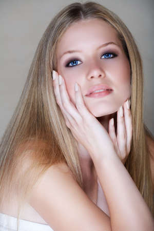 Beautiful bolond young woman in her 20s with soft smile and hands around her face Stock Photo