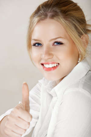 Young beautiful businesswoman with blond hair and blue eyes in white shirt showing thumbs up Stock Photo