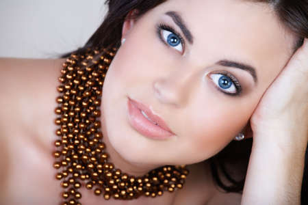 beautiful woman with brown hair and metallic bronze necklace leaning on her hand with soft smile