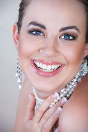 Young woman with pearl earrings and necklace laughing with an open mouth