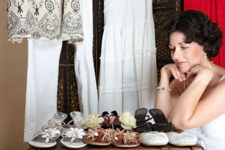 early 40s: Woman with short brown hair sitting next to her shoe collection in her mid 30s, early 40s