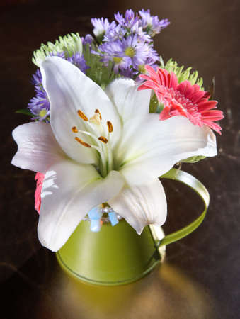 Spring bouquet of lily, gerbera and daisy flowers In a green vase � shot in natural light  photo