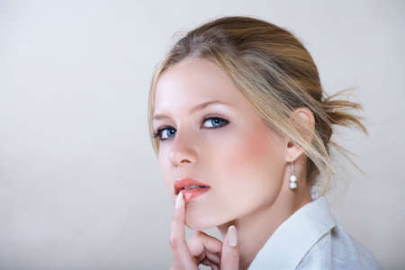 Young beautiful businesswoman with blond hair and blue eyes in white shirt holding her finger on the lips photo
