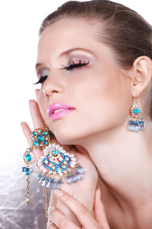 Blond woman with long false lashes holding pearl and blue stones golden jewelry with dreaming expression  - not isolated