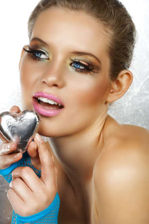 fingerless gloves: Blond beautiful woman with blue eyes and fashion make-up holding a silver heart, wearing blue fingerless gloves. Not isolated  Stock Photo