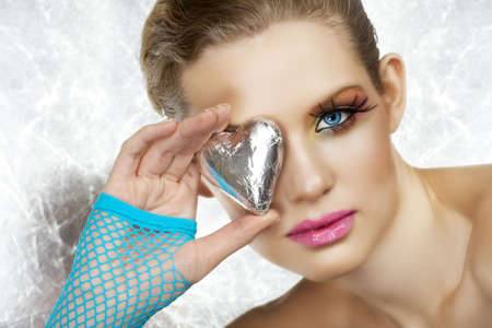Blond beautiful woman with blue eyes and fashion make-up holding a silver heart, wearing blue fingerless gloves. Not isolatedr