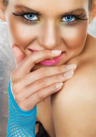 Beautiful tanned girl with fashion make-up and blue net glove, covering her cheeky smile