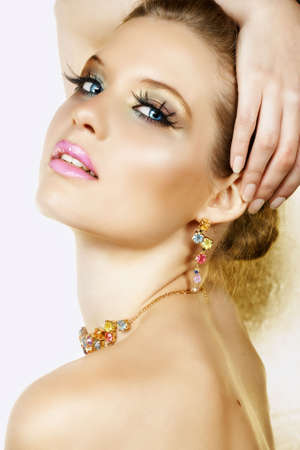 Beautiful blond woman with long lashes and colourful stones necklace and earrings and seductive smile Ð not isolated