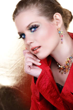 Blond woman with high-fashion make-up in red jacket holding her collar and smiling