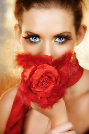 Blond beautiful woman with red silk flowers and feathers hiding her face Ð blue eyes with long lashes