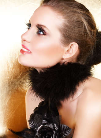 Blond woman with long false lashes in black glove and feather boa with false metallic grey rose � not isolated Stock Photo - 3146126