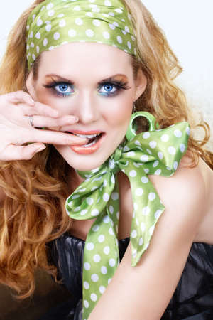 Beautiful young woman with retro green polka dot head band and bow scarf biting her finger with a smile, long feather lashes