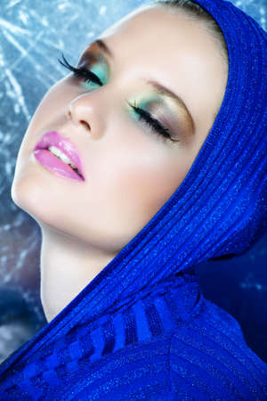 beautiful woman with long feather eyelashes in blue shiny metallic top with dreamy expression
