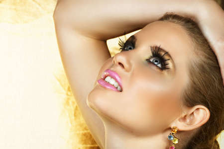 pore: beautiful woman with fantasy golden eye make-up and good skin texture and pore definition Stock Photo