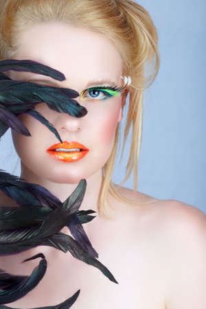Beautiful blond woman with exotic feathers and fantasy make-up, long false lashes