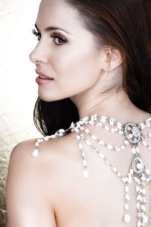 Beautiful brunette woman with white necklace on her back and soft smile - not isolated