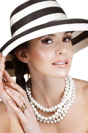Beautiful woman in black and white straw summer hat and pearls with long false eyelashes, smilingr Stock Photo
