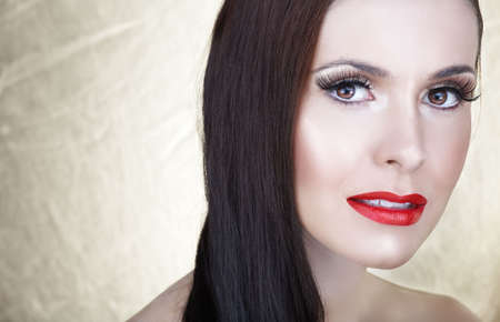 Beautiful woman with long brown hair, red lips and long false eyelashes  photo