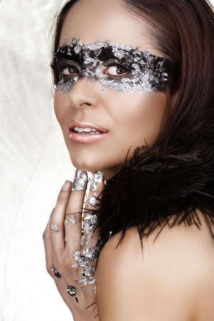 Masked beauty with silver leaf and feather boa Ð visible clean skin texture