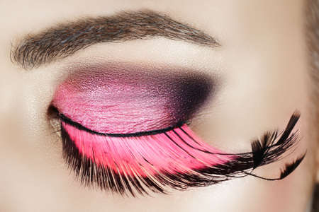 Macro eye of a woman with pink smoky eyeshadow with long feather false eyelashes