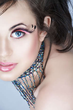 Brunette beauty with pink feather false eyelashes and full lips in pink make-up