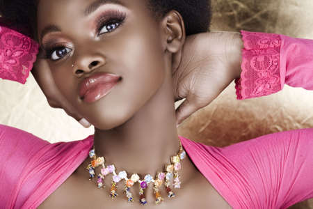 fake smile: beautiful African woman in pink summer top and long false lashes  Stock Photo