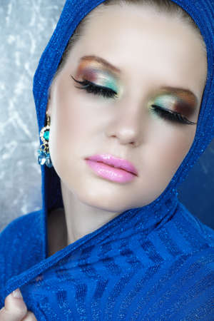highfashion: beautiful woman with long feather eyelashes in blue shiny metallic top with dreamy expression