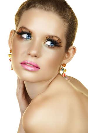 falso: Hermosa mujer rubia con pesta�as largas y coloridas piedras pendientes y seductora mirada sobre su shopudlers
