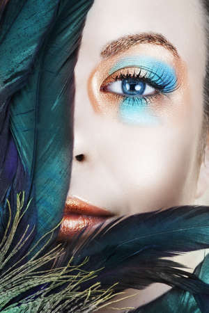 Beautiful woman with blue and bronze metallic eyeshadow, long false lashes behind peacock feathers  Stock Photo