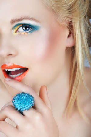 Happy blond beauty with golden and blue eyedhadow touching her orange lips  