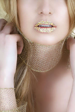 woman with gold leaf on her lips and long blond hair Stock Photo