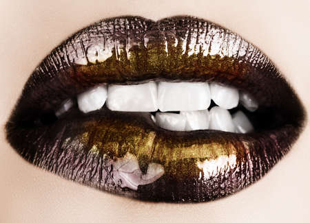 seductive: Woman biting her lips with black glossy lipstick and gold powder shine r