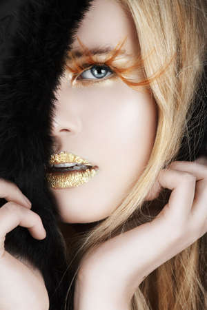 Blond beautiful woman with long hair, false feather eyelashes, fur trim and gold leaf on her lips